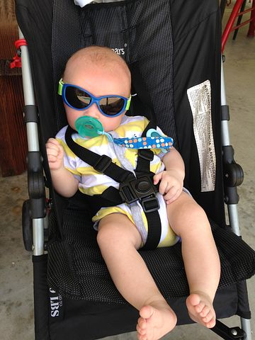 baby sitting in a baby pram wearing shades and having pacifier on mouth