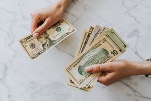 Person with money bills in hand for fast approval loan