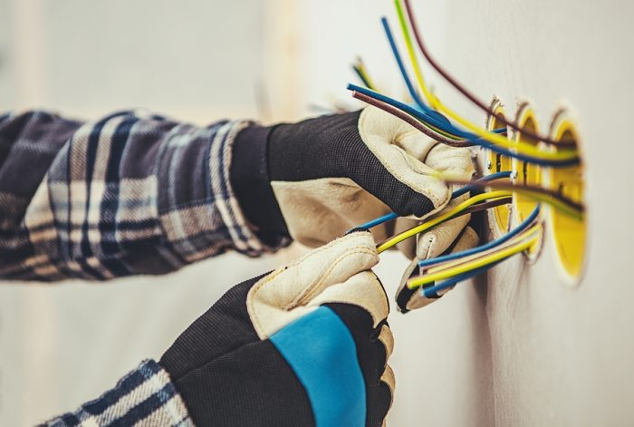 Electrician in Gold installing an electrical outlet
