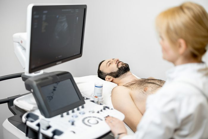 Female doctor performing a Fibroscan to a male patient